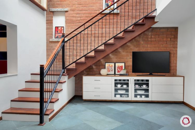 home interiors at Kengeri villa-staircase-exposed brick wall-TV unit