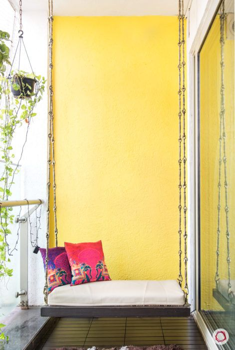 balcony-yellow-wall-swing-red-pillow-black-flooring
