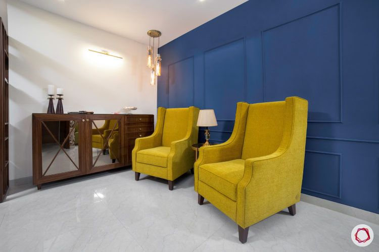 seating area-yellow wingback chair-blue accent wall-pendant light-wooden console