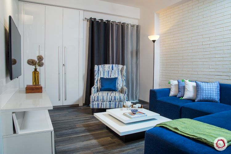 New house design-entertainment room-blue sofa-white exposed brick accent wall-white wardrobe-floor lamp