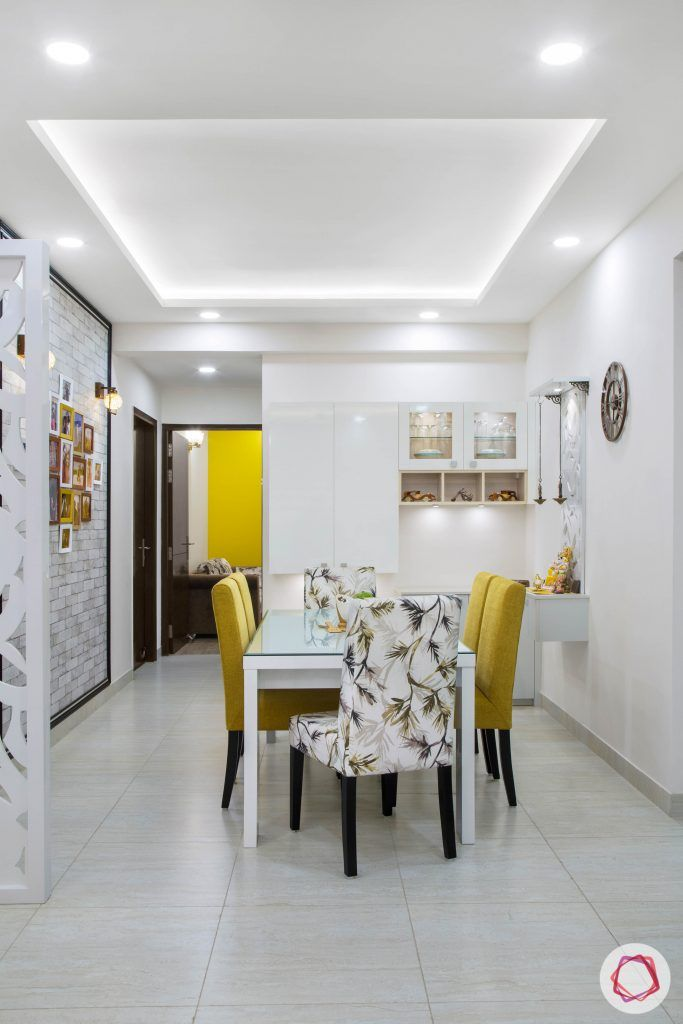 Cleo county noida_dining room with mustard yellow chairs and white crockery unit
