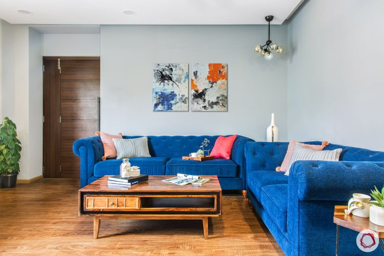 livspacehomes-low budget house-living room-blue-sofa-wooden flooring-coffee table