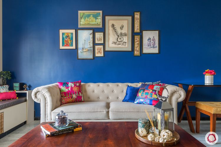livspacehomes-low budget house-artsy indian living room-sofa-blue wall-wooden centre table-window seat