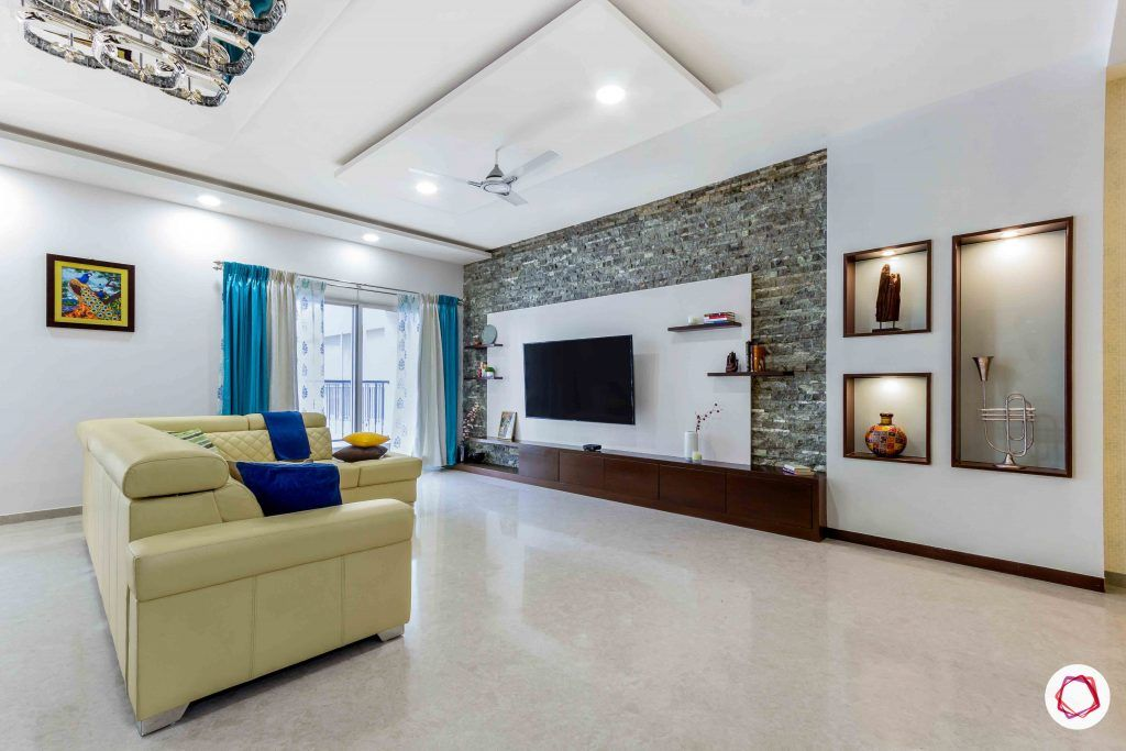 sobha forest view-living room-beige sofa-tv unit-stone wall cladding-wall niches