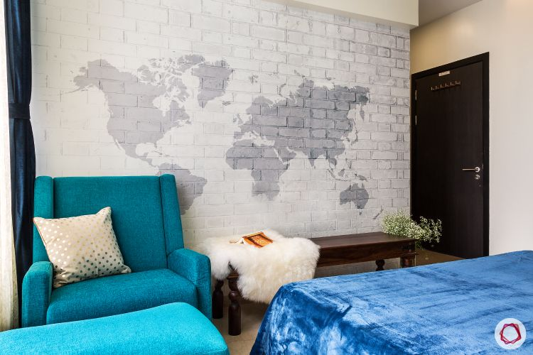 small space interior design-exposed brick wall white-world map pattern-wallpaper designs- blue fabric couch-wooden bench