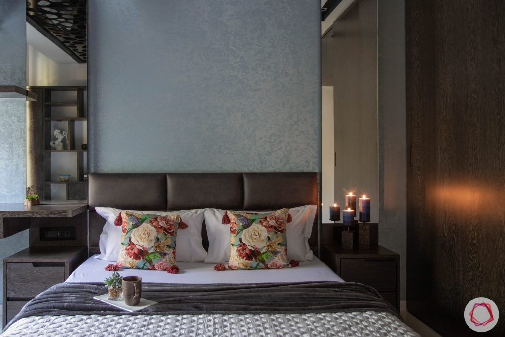 master bedroom-bed-upholstered headboard-texture wall paint-candles-bedside lamps