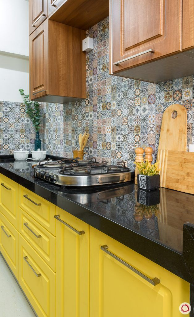 kitchen-wall-black-counter-yellow-cabinet-brown-cutting-board-stove