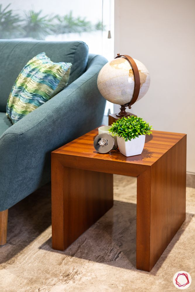 home renovation mumbai-globe-planters-wooden side table-blue couch-blue cushion