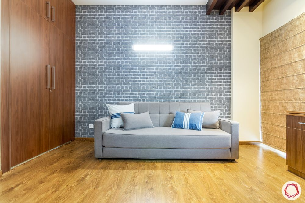 guest bedroom-sofa bed-exposed brick accent wall-wooden wardrobe
