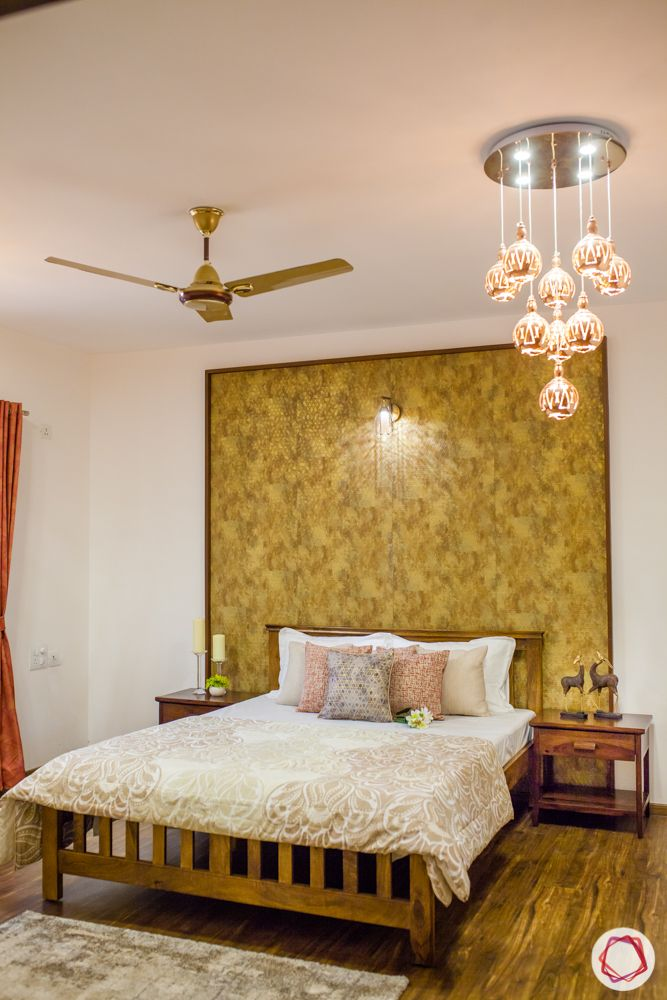 gold accent wall-wooden flooring-pendant lights-wooden bed-side table