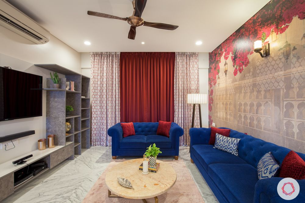 home in pune-bougainvillea wallpaper-floor lamp-blue sofa-marble center table-tv unit-grey display shelves