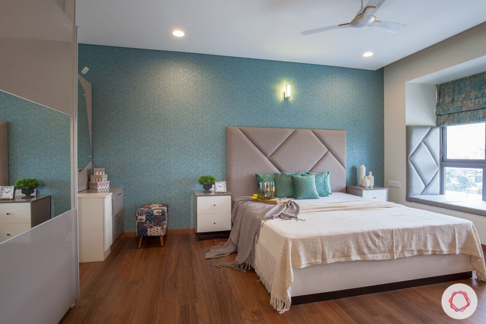 home in pune-master bedroom-teal wallpaper-bay seating-grey headboard
