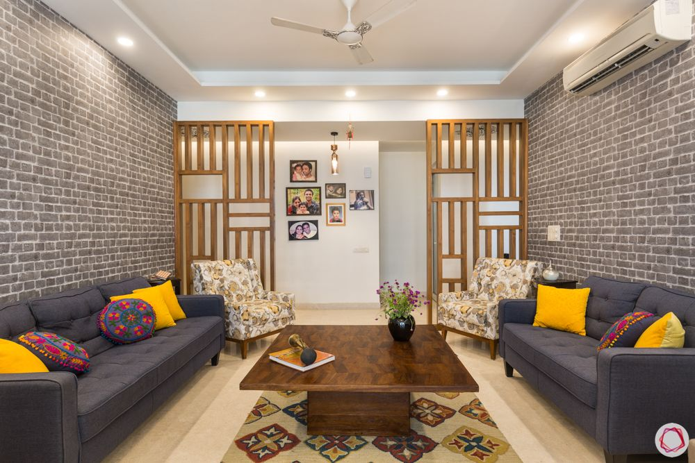 4 bhk apartment-living room-hardwood partitions-grey brick wall-grey sofa designs