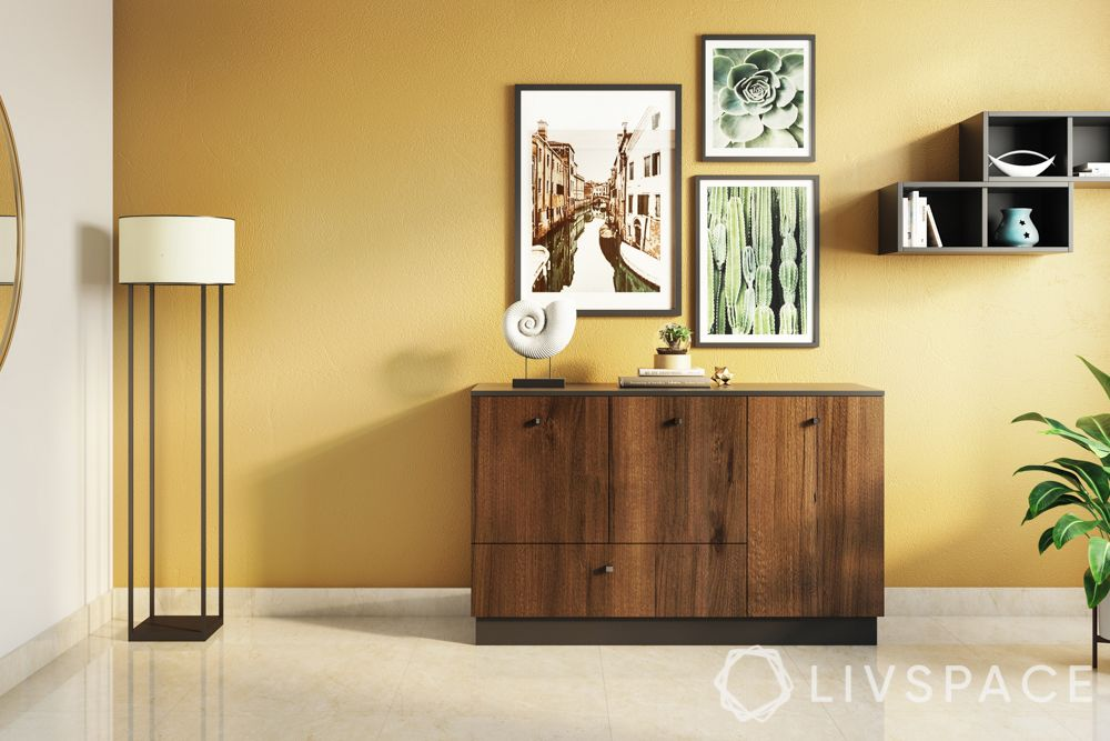 foyer design-frame pictures-table-storage-plants-yellow wall-open storage
