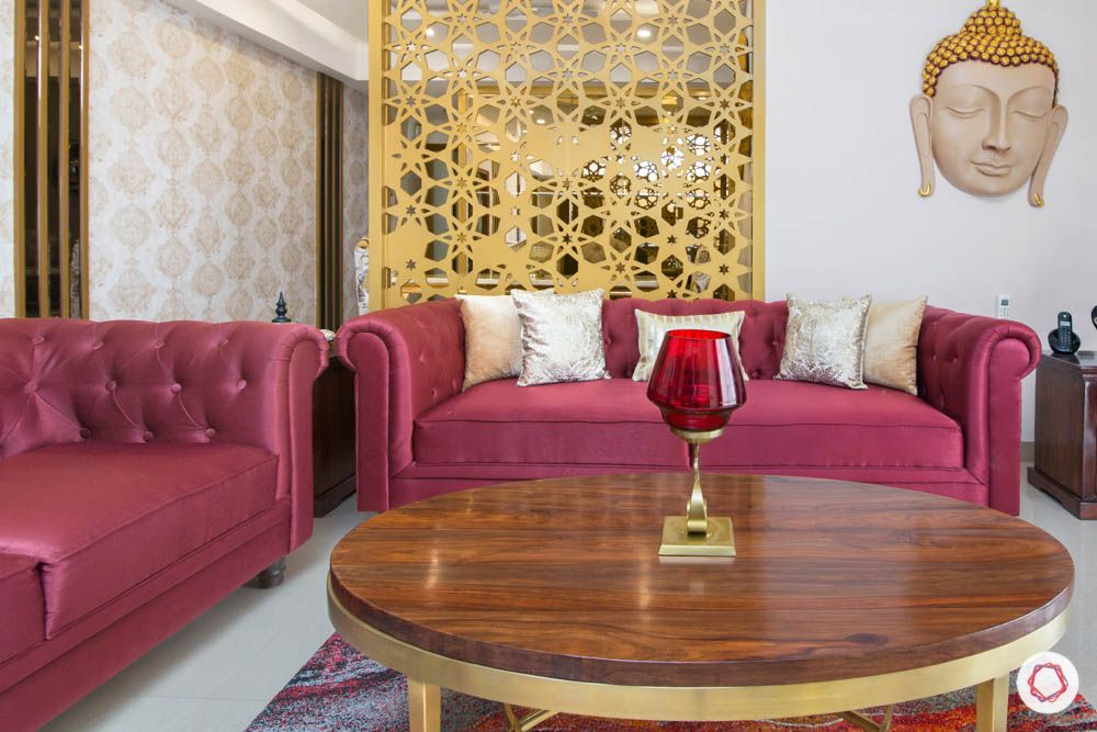 jewel toned interiors-red sofa-gold partition-wooden coffee table