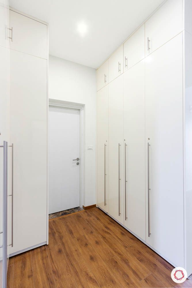 walk in closet-wardrobe designs-white swing doors-wooden flooring