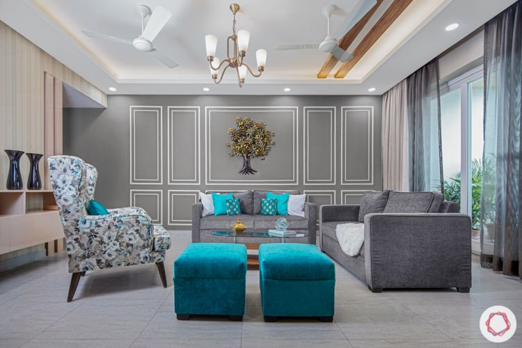 Living room colours-grey walls-chandelier-accent chair-blue pouf-grey sofa