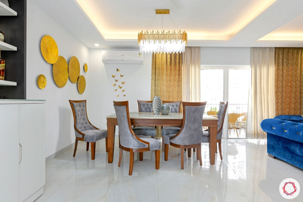 4 bhk home design-chandelier-velvet dining table