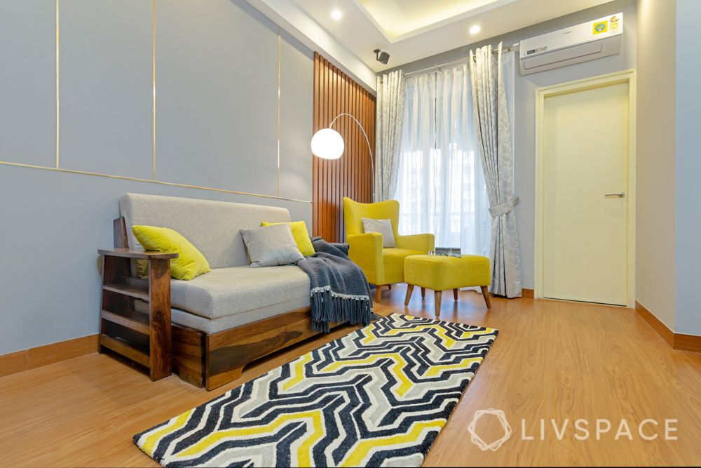 yellow accent chair-rug-floor lamp-sofa-gallery wall-wooden panelling