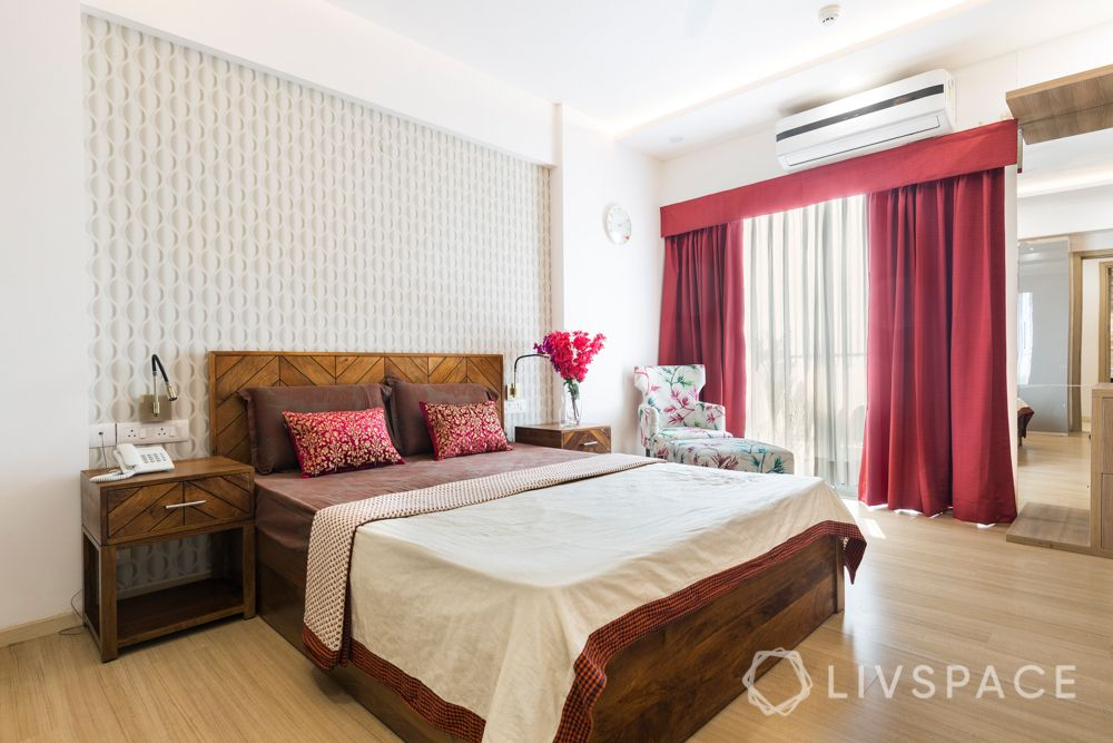 Master bedroom-patterned wallpaper-maroon curtains-wooden furniture