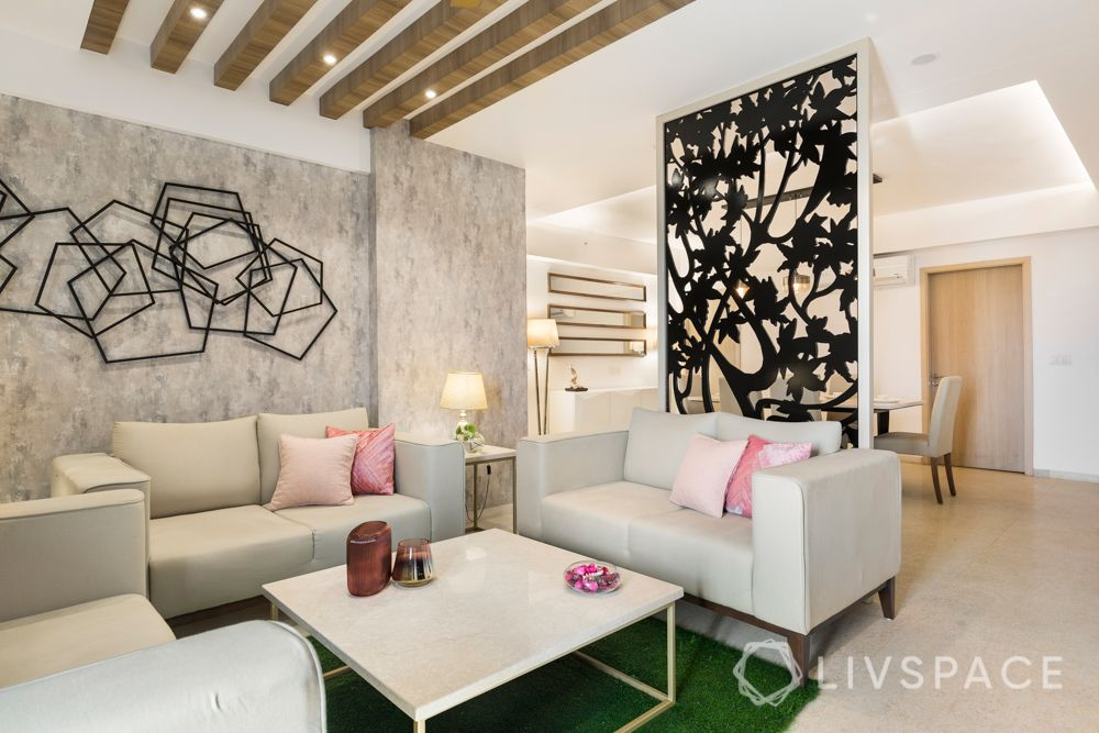 wooden rafters-ceiling designs-metallic wall accessories-cream sofa-grey wallpaper-table lamps-artificial turf-jaali partition