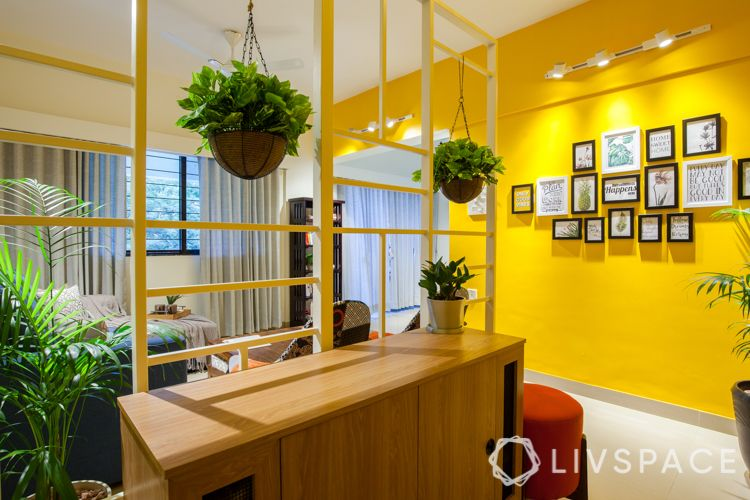 small house interior design-yellow wall-red ottoman-track lights-framed wall