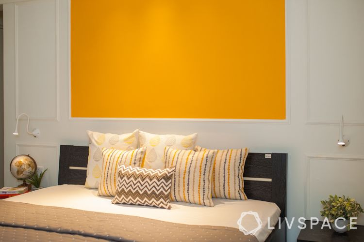 small house interior design-yellow wall-wall trims-track lights-bedside lights