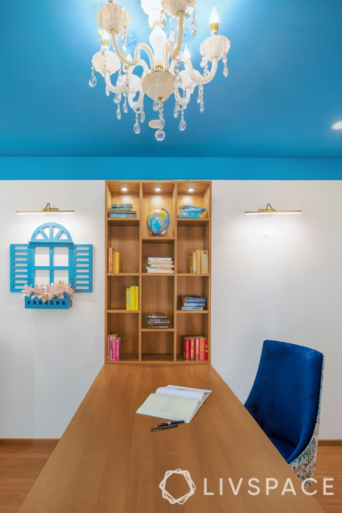 travel-themed interior design-blue and white chair-wooden desk and bookshelf-painted ceiling-white walls