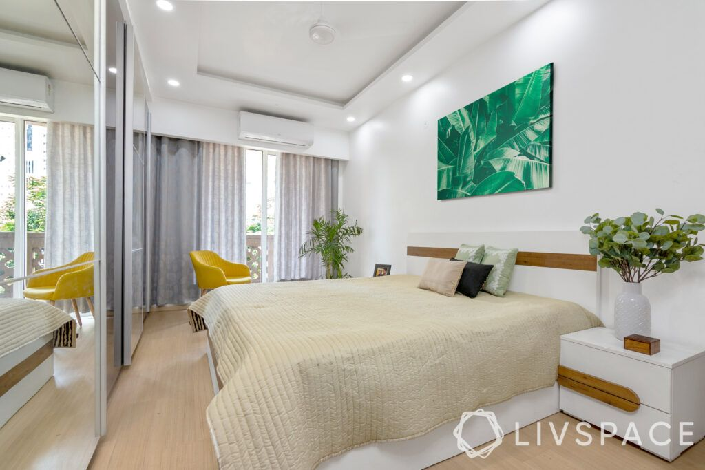 interior design on a budget-bedroom-basic false ceiling-yellow chair-side table-mirror wardrobe