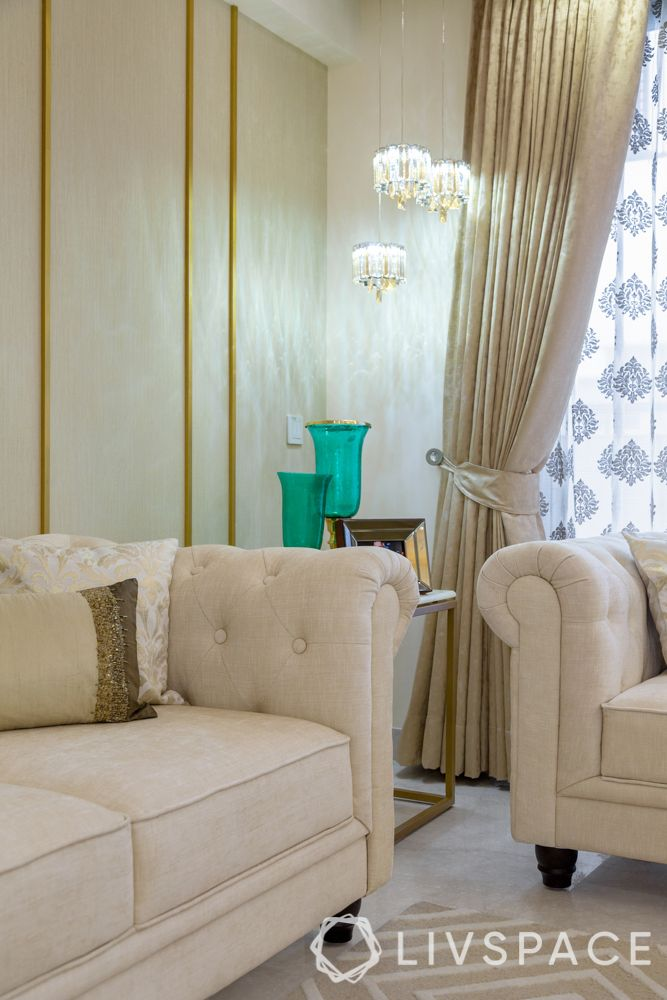 interior design company in gurgaon-living room-neutral sofa-pattern rug-gold wall trims-textured wallpaper