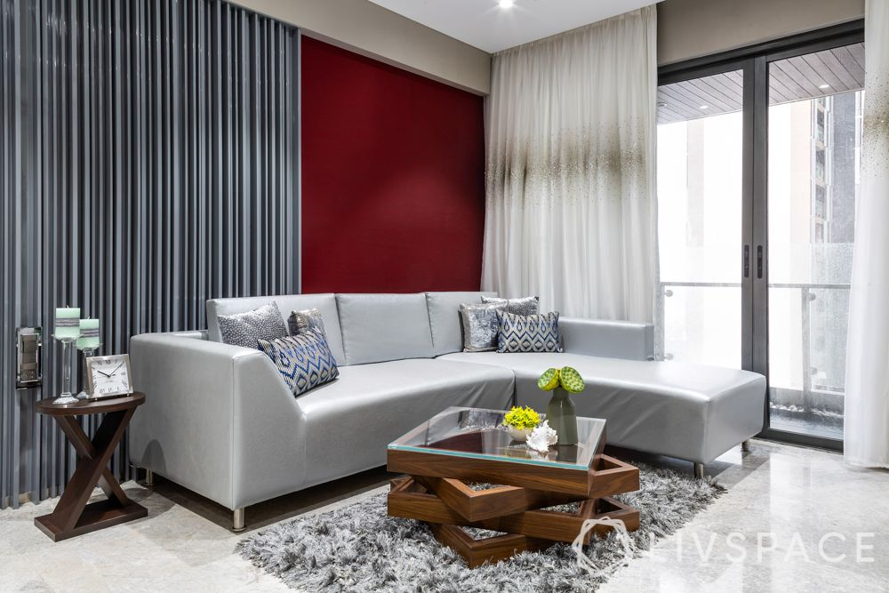 Compact home-living room-silver sofa-maroon accent wall-centre table-rug