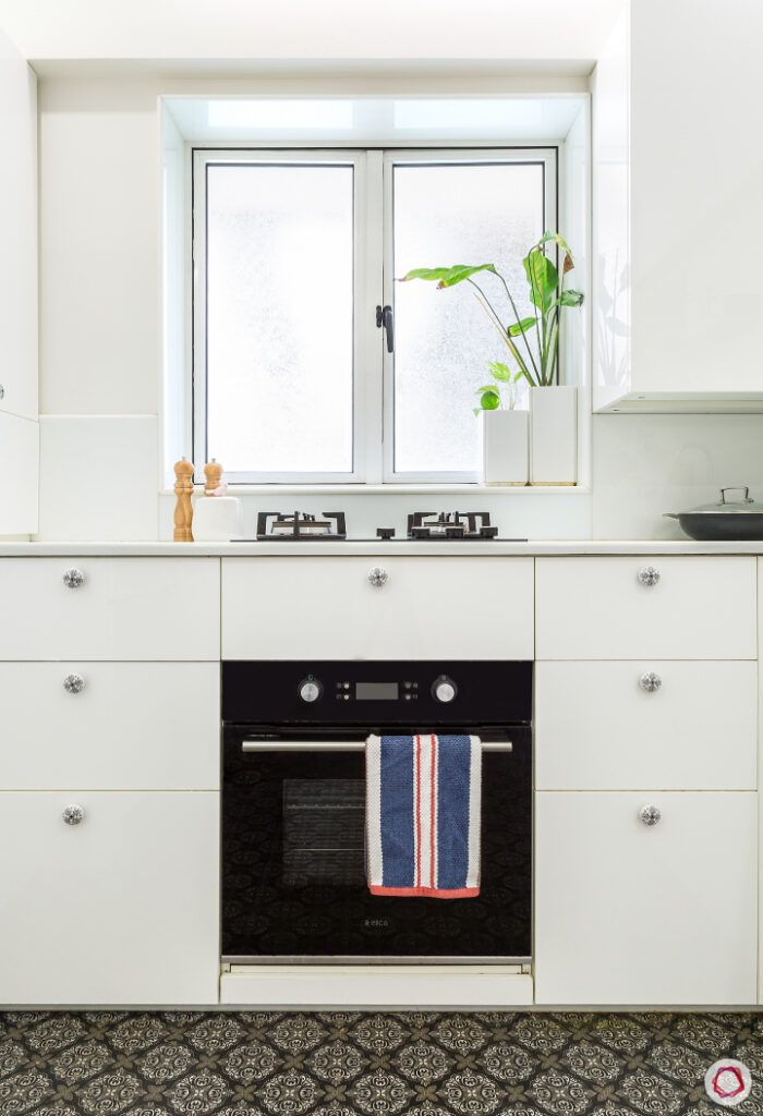 maintain white kitchens-white cabinets-plant vase-stove-kitchen window