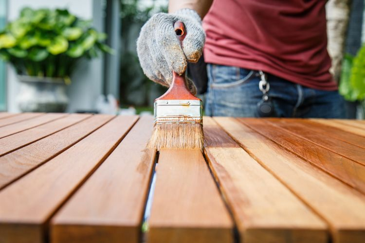 man-applying-fresh-paint-table-wooden-slats