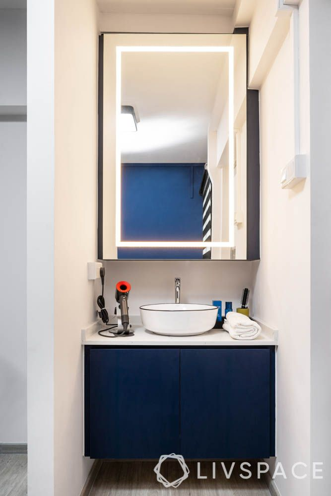 HDB bathroom designs_lighting_dark blue cabinet doors_white counterop_lighted mirror