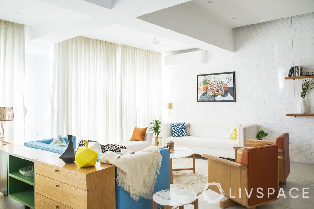 Livspace-orange chairs-rug-pendant lights-blue wall-wall art